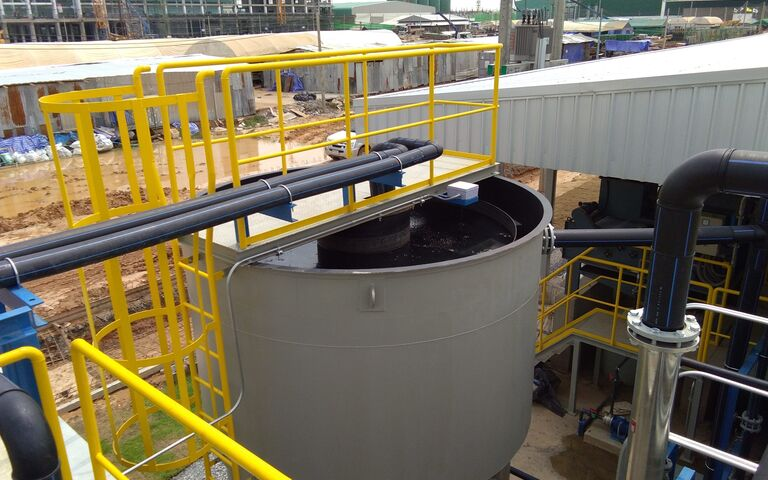 Small, steel cylindrical sludge sedimentation tank with a conical base and yellow railings on the platform above it