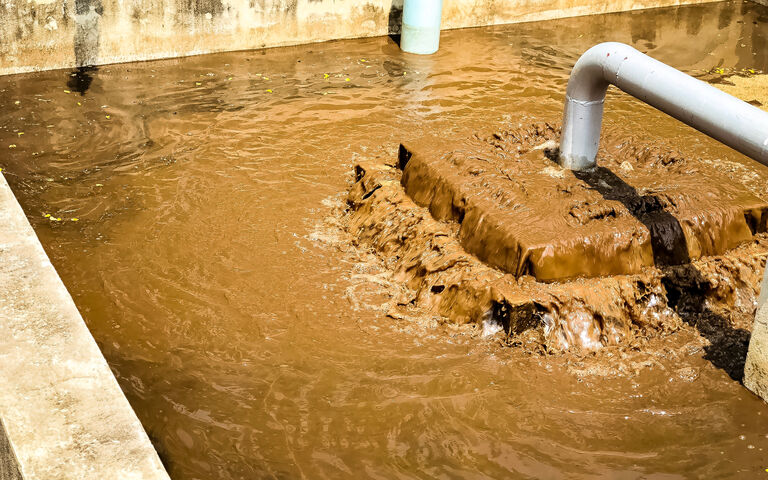 Sludge treatment in wastewater treatment. Brown liquid flowing in a concrete tank with pipes